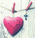 装饰红色心脏和小金属钥匙在一条绳索以一个老白板为背景 免版税库存照片