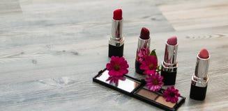 装饰舱内甲板放置与妇女化妆用品和花的构成 平的位置,在白色背景的顶视图,组成 免版税库存照片