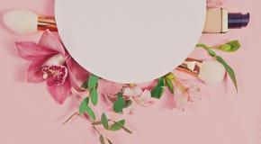 装饰舱内甲板放置与构成产品、化妆用品和花的构成 平的位置,在桃红色背景的顶视图 图库摄影