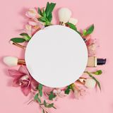 装饰舱内甲板放置与构成产品、化妆用品和花的构成 平的位置,在桃红色背景的顶视图 免版税图库摄影