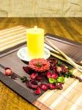 装饰花和叶子和一个黄色蜡烛在桌上的红色,绿色家的构成 免版税库存照片