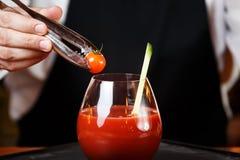 装饰血玛莉酒或凯撒鸡尾酒的侍酒者在酒吧 库存图片