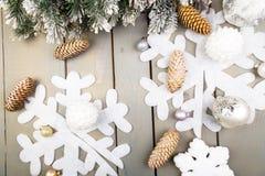 装饰雪花、圣诞树和锥体在木背景 看板卡圣诞节问候 复制空间 顶视图 平的位置 免版税库存照片