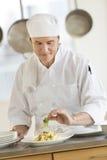 装饰面团盘的厨师在餐馆厨房里 图库摄影