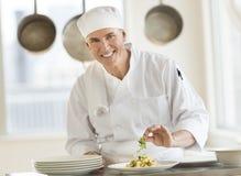 装饰面团盘的愉快的厨师画象 免版税库存照片
