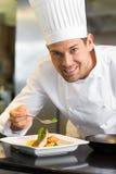 装饰食物的微笑的男性厨师在厨房里 免版税库存图片