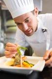 装饰食物的被集中的男性厨师在厨房里 免版税库存照片
