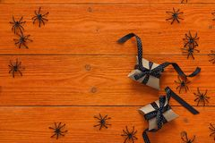 装饰黑蜘蛛和礼物盒在橙色木板 免版税图库摄影