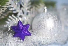 装饰紫罗兰色玩具雪花和一个银色新年球在焦点外面 免版税库存图片