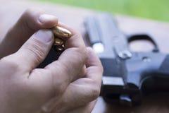 装货手枪杂志 子弹和手枪背景 充电的枪 库存照片
