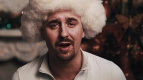 裘皮帽唱歌坐的未剃须的歌手在有圣诞节装饰的屋子里 影视素材