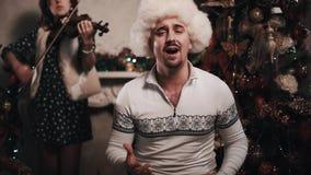 裘皮帽的人唱歌与弦乐四重奏的坐在屋子里在圣诞树附近 股票录像