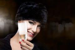 裘皮帽的冬天时尚少妇敬酒与香宾的 免版税库存照片