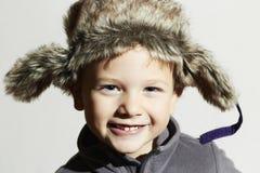 裘皮帽的微笑的孩子 时尚偶然冬天样式 滑稽的男孩一点 儿童情感 免版税库存图片