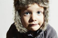裘皮帽的滑稽的孩子 偶然冬天样式 大蓝眼睛 免版税库存照片
