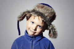 裘皮帽的滑稽的孩子 蓝色体育毛线衣的小男孩 儿童情感 免版税库存照片