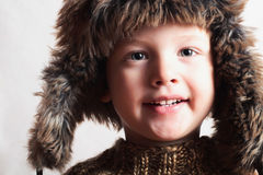 裘皮帽的滑稽的微笑的孩子。时尚孩子。冬天样式。小男孩。孩子 库存照片