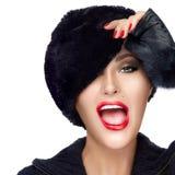 裘皮帽覆盖物眼睛的畏缩冬天时尚的少妇 图库摄影