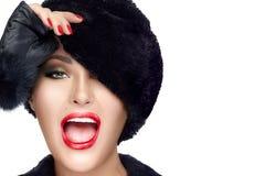 裘皮帽覆盖物眼睛的畏缩冬天时尚的少妇 免版税图库摄影