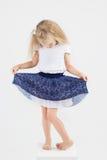 裙子的逗人喜爱的小女孩在立方体 免版税库存照片