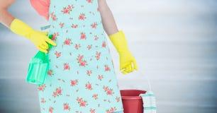 围裙的妇女下体与反对模糊的灰色木盘区的桶 库存照片
