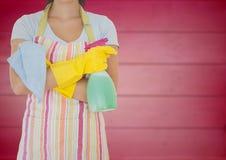 围裙的妇女与双臂被交叉和擦净人反对模糊的桃红色木盘区 免版税库存图片