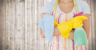 围裙的妇女与反对模糊的木盘区的擦净剂 免版税库存照片
