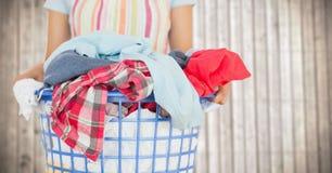 围裙的妇女与反对模糊的木盘区的洗衣店 库存图片