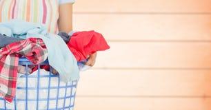 围裙的妇女与反对模糊的橙色木盘区的洗衣店 图库摄影