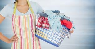 围裙的妇女与反对模糊的灰色木盘区的洗衣店 免版税库存图片