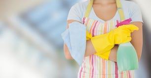 围裙的妇女与反对模糊的窗口的擦净剂 免版税库存图片