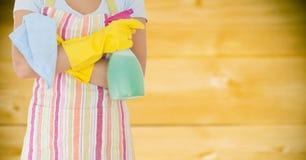 围裙的妇女与反对模糊的黄色木盘区的擦净剂 免版税库存照片