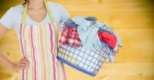 围裙的妇女与反对模糊的黄色木盘区的洗衣店 免版税图库摄影