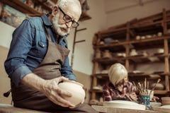 围裙的审查有妇女工作的资深陶瓷工和镜片陶瓷碗 图库摄影