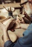 围裙的审查陶瓷碗的资深陶瓷工和镜片 库存照片