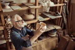围裙的审查陶瓷碗的资深陶瓷工和镜片 图库摄影