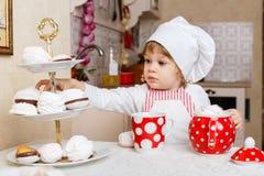 围裙的小女孩在厨房里。 免版税库存图片