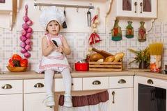 围裙的小女孩在厨房里 免版税库存图片