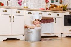 围裙的小女孩在厨房里 免版税图库摄影