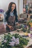 围裙的微笑的非裔美国人的妇女拿着剪枝夹和与花店的新鲜的植物一起使用 图库摄影
