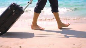 裤子和一件经典衬衣的一年轻人带着手提箱沿海滩走反对绿松石海的背景 股票录像