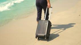 裤子和一件经典衬衣的一年轻人带着手提箱沿海滩走反对绿松石海的背景 影视素材