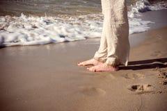裤子的妇女由海走 免版税库存照片