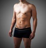 黑裤子的年轻性感的英俊的人 免版税库存图片