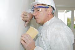 裱糊墙壁的男性工作者沙子 库存图片