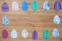 裱糊色的复活节彩蛋被安排在一个木板的一个长方形框架 免版税库存照片