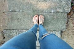 裸体穿上鞋子妇女和黄色菠萝衬衣辅助部件 关闭在女孩佩带裸体凉鞋和缺乏在S的蓝色牛仔裤的` s脚 免版税库存照片