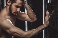 裸体英俊的人在墙壁倾斜并且有一场冷的阵雨 免版税库存照片