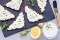 裸麦粉粗面包面包用希脂乳,乳脂干酪,迷迭香,柠檬,大蒜垂度 库存图片