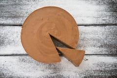 褐巧克力色乳酪蛋糕和切片在木桌上 图库摄影